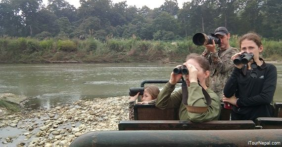 Family with kids watching wildlife in Chitwan National park.